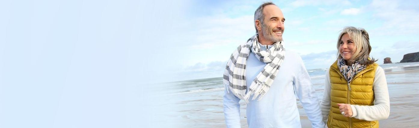 Older couple walking on the beach | Dental Implants Poway CA